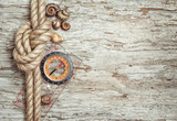 Ship rope, shells, compass and wood background