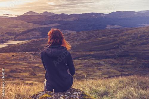 Fotografija  Woman sitting on mountain top and contemplating