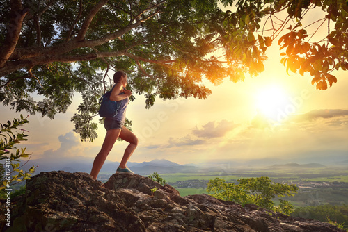 Fotografie, Obraz  Young woman admires the sunset with a backpack standing on cliff