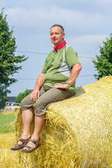 Naklejka na ściany i meble Farmer sitting on straw bales