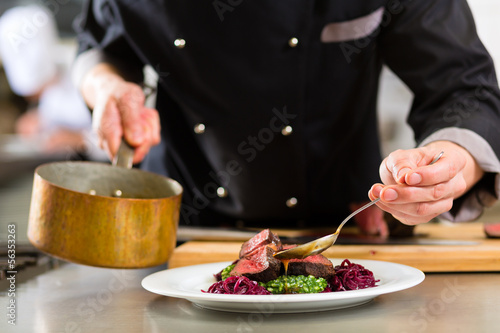 Fototapeta Chef in hotel or restaurant kitchen cooking obraz