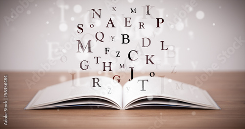 Opened book with flying letters