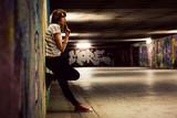 Fototapeta Młodzieżowe - Stylish girl standing in grunge graffiti tunnel, shanty town