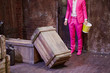 Man in pink suit and shoes stands with big bucket of popcorn