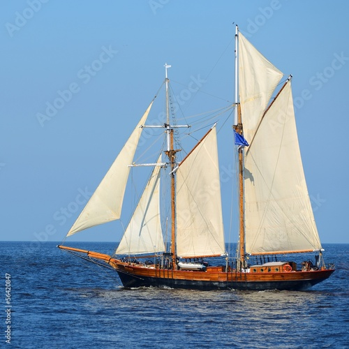 Cadres-photo bureau Navire old historical tall ship (yacht) with white sails in blue sea