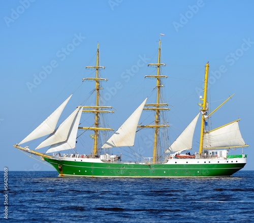 Keuken foto achterwand Schip old historical green tall ship with white sails in blue sea