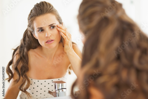 Concerned woman checking facial skin condition in bathroom
