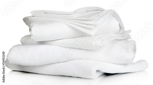 Fototapeta Stack of clean bedding sheets and towels isolated on white