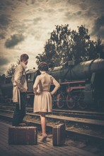 Beautiful  Couple With Suitcases On  Train Station