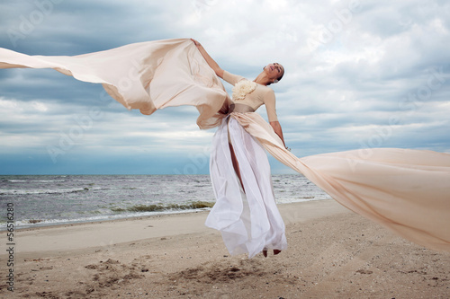 Obraz na plátně  model jumps with long dress like a wings at the beach