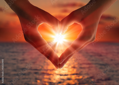 Fototapeta sunset in heart hands obraz