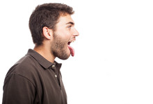 Young Man Showing His Tongue On A White Background