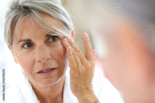 Senior woman applying anti-wrinkles cream Fototapet