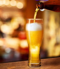 Pouring Beer In Glass On Bar O...