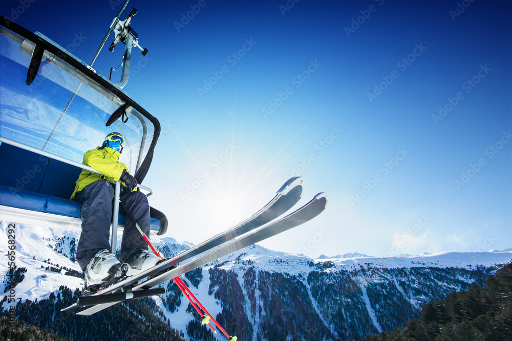 Fototapety, obrazy: Skier siting on ski-lift - lift at sunny day and mountain