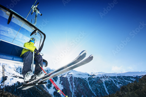 Garden Poster Winter sports Skier siting on ski-lift - lift at sunny day and mountain