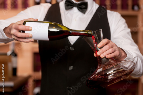 Photo Sommelier with decanter. Cropped image of sommelier pouring wine