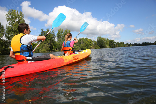 Couple riding canoe in river Fototapete