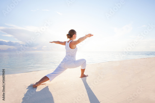 Fotografia  Caucasian woman practicing yoga at seashore