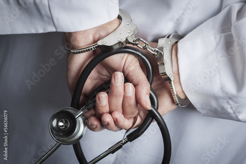 Fotografie, Obraz  Female Doctor or Nurse In Handcuffs Holding Stethoscope