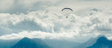 Paraglider over mountains and cloudy sky background - 56669463