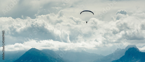 Poster de jardin Aerien Paraglider over mountains and cloudy sky background