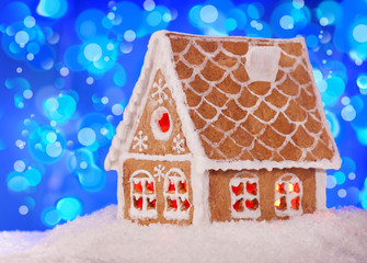 Gingerbread house in the snow with a beautiful New Year's backgr
