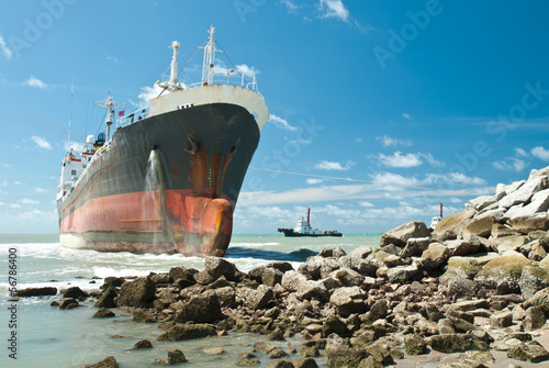Foto op Plexiglas Schipbreuk Cargo ship run aground on rocky shore