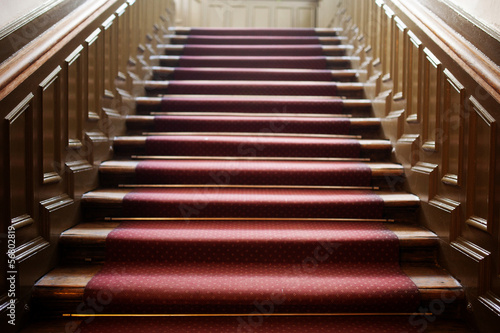 Empty wooden staircase with red carpet
