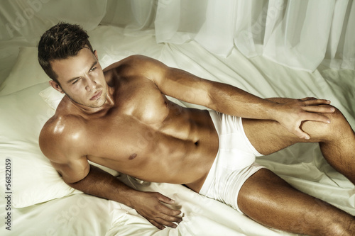 Handsome nude man lying in a bed.