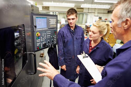 Fotografía  Engineer Teaching Apprentices To Use Computerized Lathe