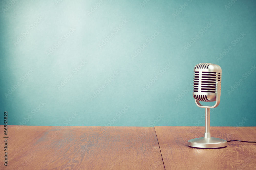 Retro style microphone on table in front aquamarine wall