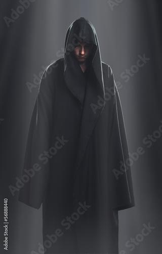 a guy in a black robe standing in the dark Fototapeta