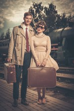 Beautiful Vintage Style Couple With Suitcases On  Train Station