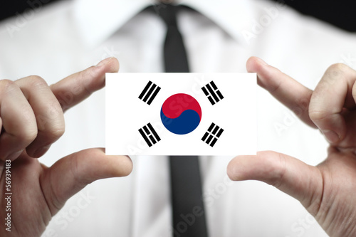 Fotografía  Businessman holding a business card with South Korea Flag