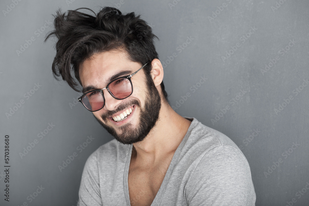 Fototapeta sexy man with beard smiling big against wall