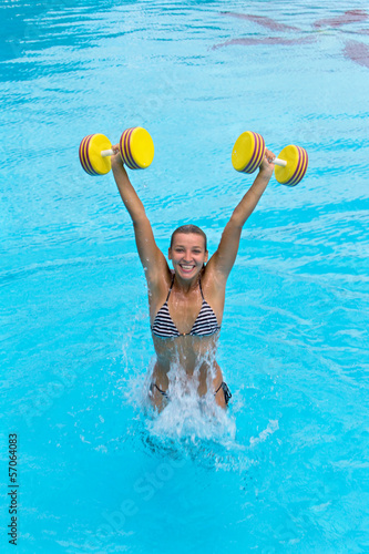 Fotografie, Obraz  Woman is engaged aqua aerobics with dumbbells in water