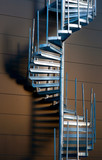 Metal spiral staircase casting shadow on wall in evening light