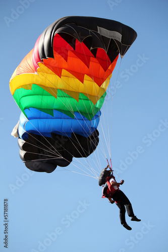 Valokuva parachutist with colorful parachute on blue sky