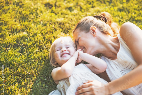 Leinwand Poster Happy mother and baby laying on meadow