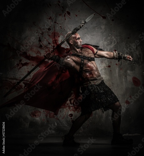 Wounded gladiator in red coat throwing spear Fototapeta