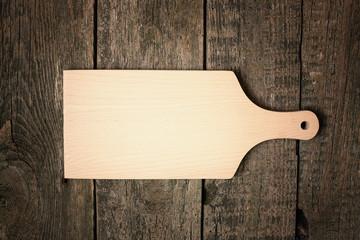 Pusta deska do krojenia na starym drewnianym tle.