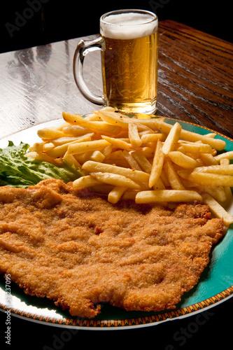 Fotografia cotoletta alla milanese con patate fritte e birra