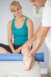 Physiotherapist examining patients leg