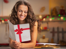 Happy Young Housewife Reading Christmas Postcard In Kitchen