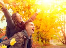 Happy Couple In Autumn Park. Fall. Family Having Fun Outdoors