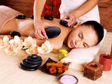 Adult woman having hot stone massage in spa salon