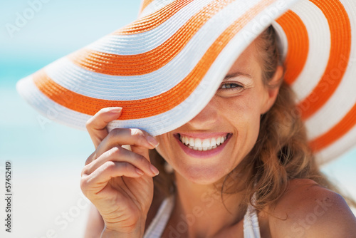 Obraz Portrait of happy young woman in swimsuit and beach hat - fototapety do salonu