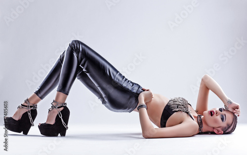 Fotografija  sexy woman in leather pants laying down on a white background