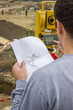 Land surveyor analyzing a cadastral and site plans on constructi